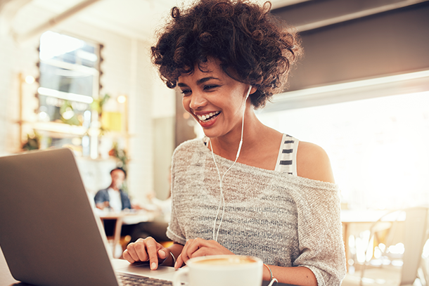 Photo of woman smiling while looking at her computer.