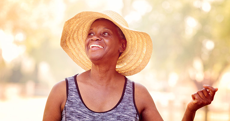Woman walking in a park and smiling.