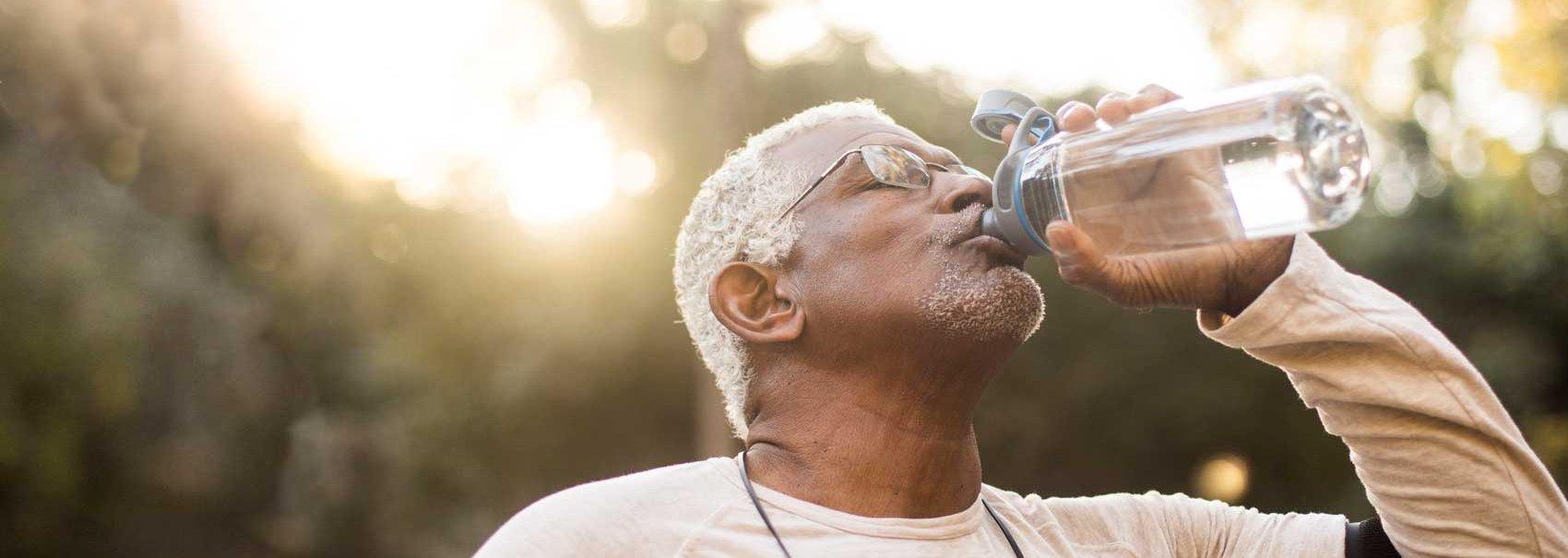 Hombre bebiendo agua mientras hace ejercicio para el mes de la salud del hígado