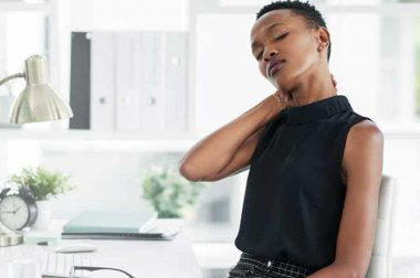 Woman at desk rubbing back of neck