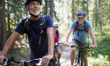 Dos personas sonriendo mientras andan en bicicleta en el bosque