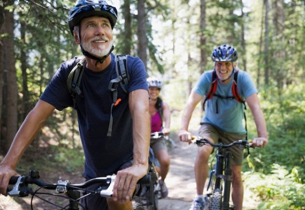 Two people smiling while riding bikes in the forest